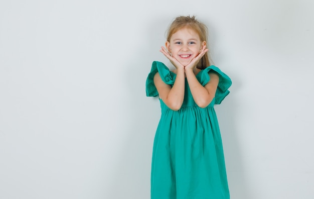 Kleines mädchen, das hände unter kinn im grünen kleid hält und niedlich schaut