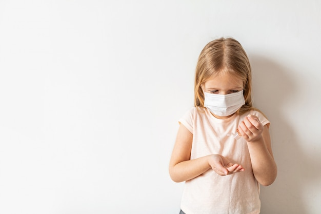 Kleines mädchen, das händedesinfektionsalkoholgel für saubere hände verwendet
