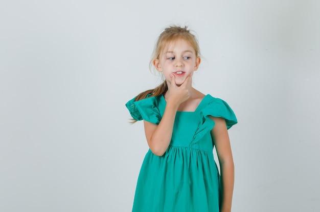 Kleines mädchen, das hand am kinn im grünen kleid hält und niedlich schaut. vorderansicht.