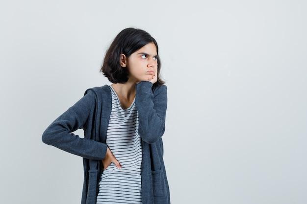 Kleines mädchen, das hand auf wange im t-shirt, in der jacke hält und düster aussieht.