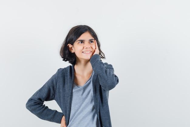 Kleines mädchen, das hand auf wange im t-shirt, in der jacke hält und verträumte vorderansicht schaut.