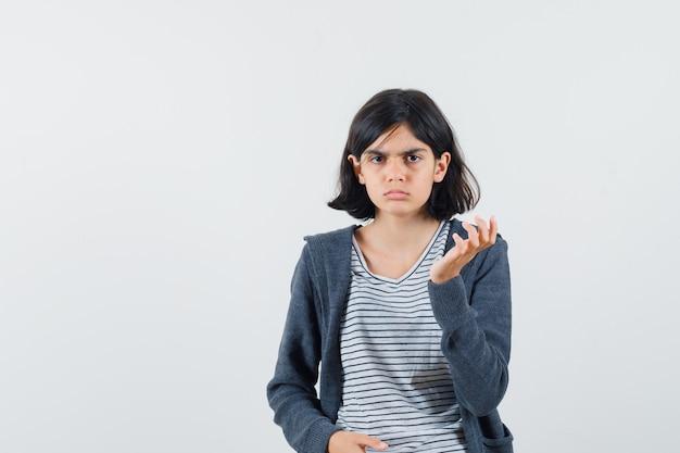 Kleines mädchen, das hand erhebt, während es im t-shirt, in der jacke aufwirft und ernst schaut