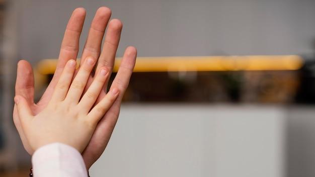 Kleines mädchen, das hand mit der ihres vaters vergleicht