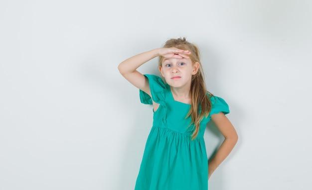 Kleines mädchen, das hand über augen im grünen kleid hält