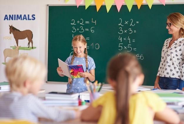 Kleines mädchen, das hausaufgaben im klassenzimmer liest