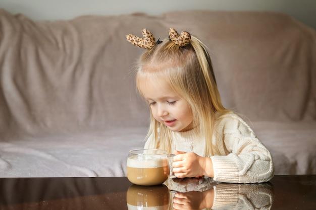 Kleines mädchen, das heißen kakao trinkt