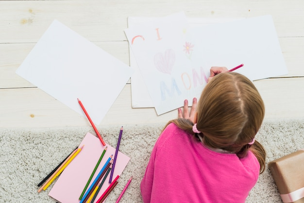 Kleines mädchen, das ich mamma auf papier zeichnet