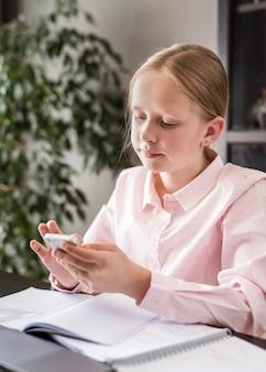 Kleines mädchen, das ihr telefon in der online-klasse überprüft