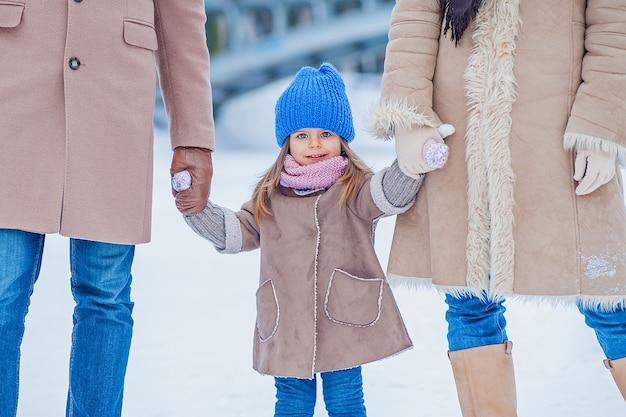 Kleines mädchen, das ihre eltern im winter auf dem hintergrund eines gefrorenen sees und einer brücke hält