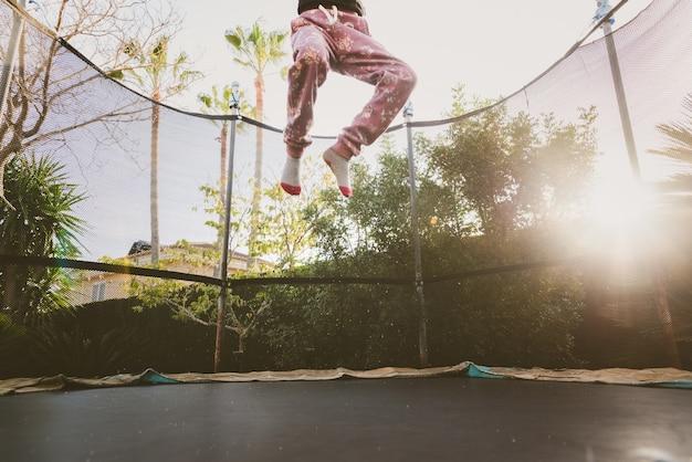 Kleines mädchen, das ihre ferien draußen springen auf die trampoline tut akrobatische übung genießt.