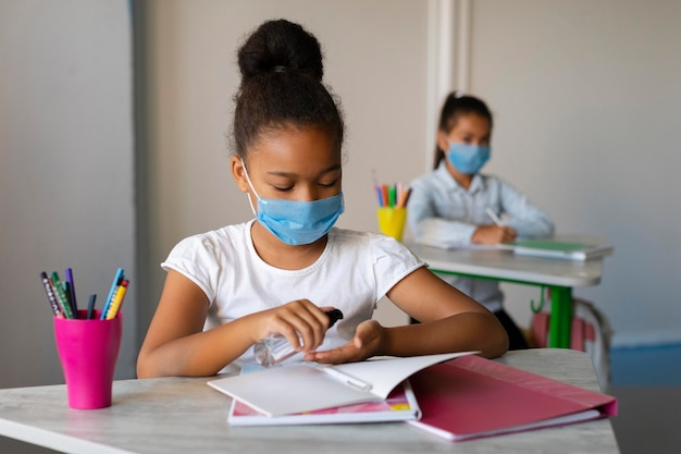 Kleines mädchen, das ihre hände im unterricht desinfiziert