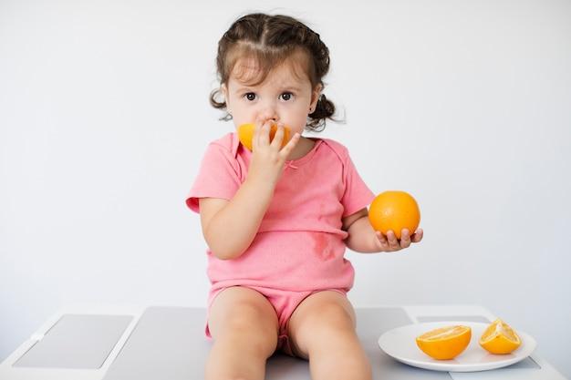 Kleines mädchen, das ihre orangen sitzt und genießt