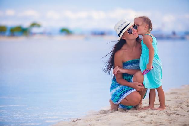 Kleines mädchen, das ihre schöne mutter auf einem weißen tropischen strand küsst