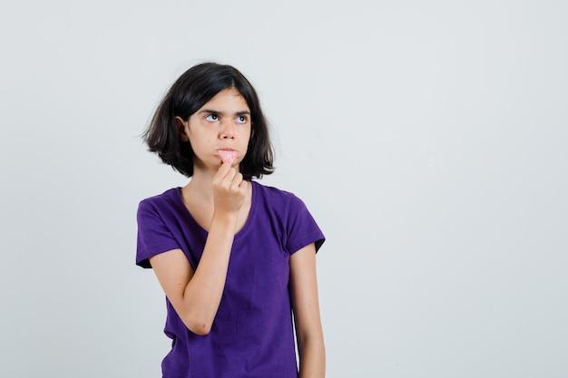 Kleines mädchen, das ihre zunge hält, ragte in t-shirt heraus und sah verwirrt aus.