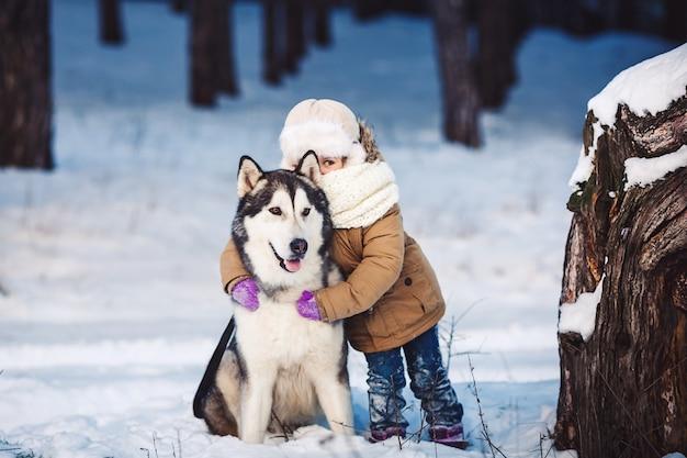 Kleines mädchen, das ihren großen malamute-hund umarmt