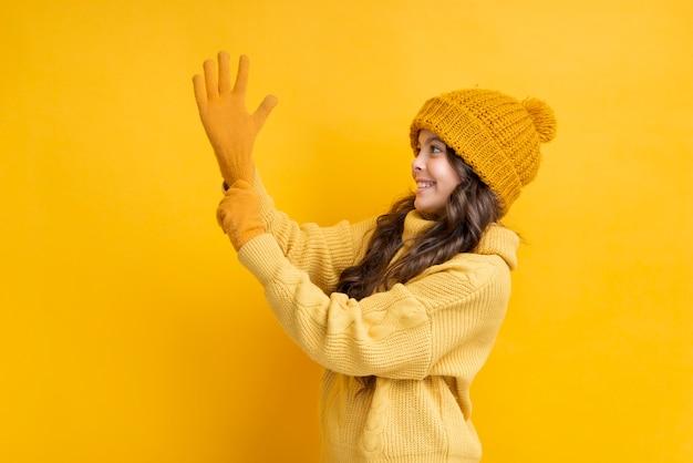 Kleines mädchen, das ihren handschuh auf ihrer hand zieht