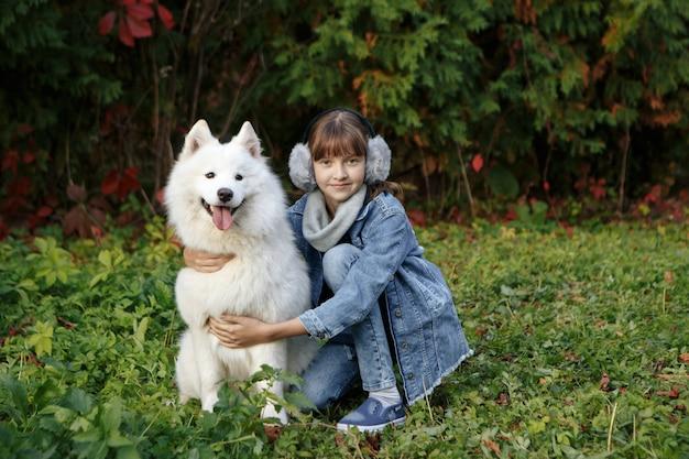 Kleines mädchen, das ihren hund in einem park umarmt