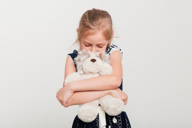 Kleines mädchen, das ihren teddybären umarmt