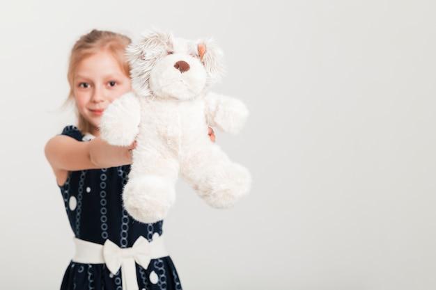 Kleines mädchen, das ihren teddybären zeigt