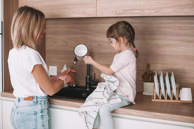 Kleines mädchen, das ihrer mutter beim geschirrspülen in der küche hilft. frau spült das geschirr, ihre tochter wischt die tasse mit einem handtuch ab.