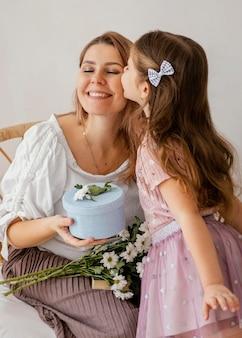 Kleines mädchen, das ihrer mutter frühlingsblumen und geschenkbox für muttertag gibt