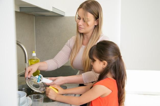 Kleines mädchen, das ihrer mutter hilft, geschirr zu spülen. mutter und tochter stehen nahe küchenspüle und erledigen hausarbeit.