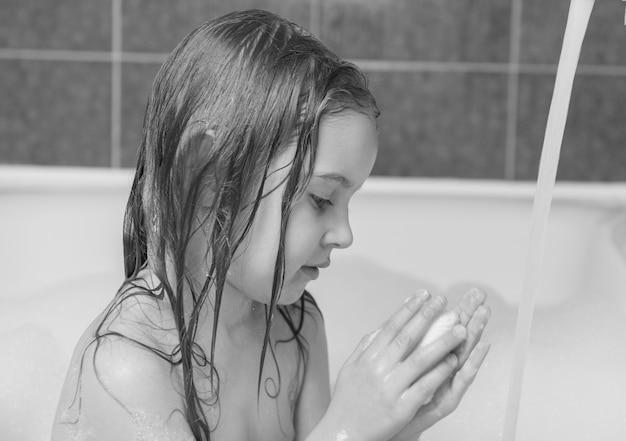Kleines mädchen, das im bad spielt