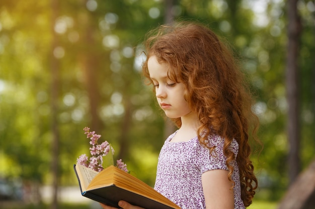Kleines mädchen, das im frühjahr einen park des buches liest.