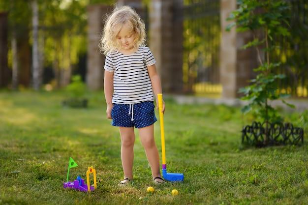 Kleines mädchen, das im frühjahr park des minigolfs spielt