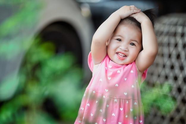 Kleines mädchen, das im lokalen thailand des parks spielt und lächelt