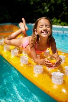 Kleines mädchen, das im schwimmbad entspannt, sonnenbräune genießt, trinkt einen saft auf aufblasbarer gelber matratze im wasser im familienurlaub