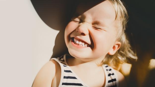 Kleines mädchen, das im sonnenlicht lächelt und schielt, glückliches kleinkind, das spaß hat