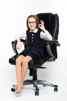 Kleines mädchen, das im stuhl zeigt das okayzeichen gekleidet als geschäftsfrau sitzt
