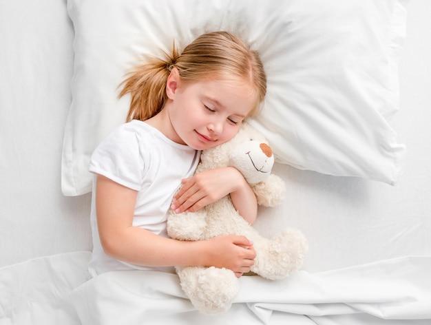 Kleines mädchen, das im weißen bett schläft
