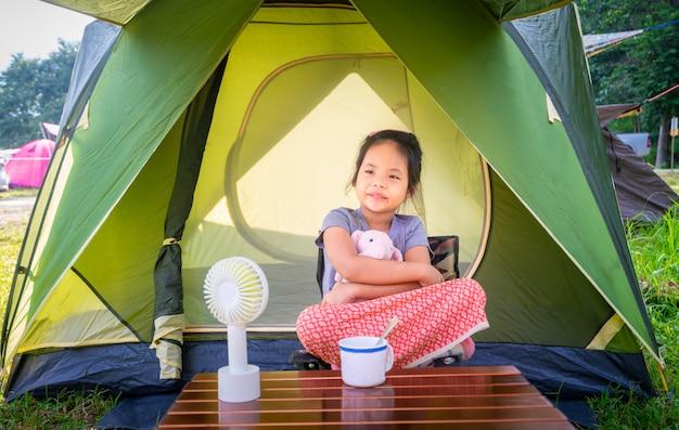 Kleines mädchen, das im zelt beim kampieren gehen sitzt das konzept von tätigkeiten und von abenteuern im freien in der natur.