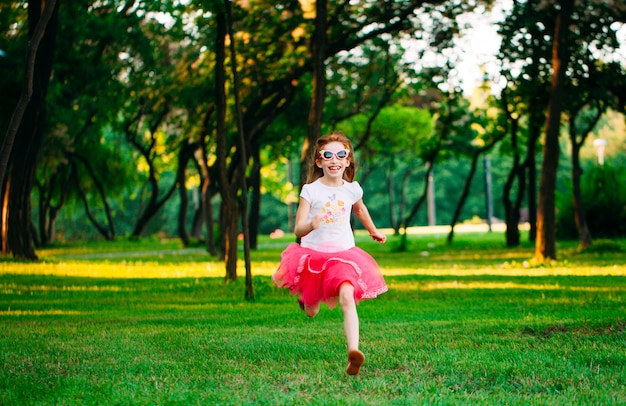 Kleines mädchen, das in den park läuft