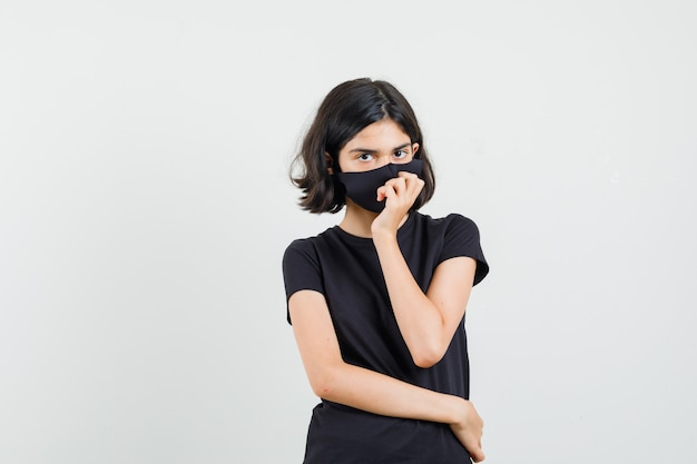 Kleines mädchen, das in der denkenden haltung im schwarzen t-shirt, in der maske und in der vernünftigen vorderansicht steht.