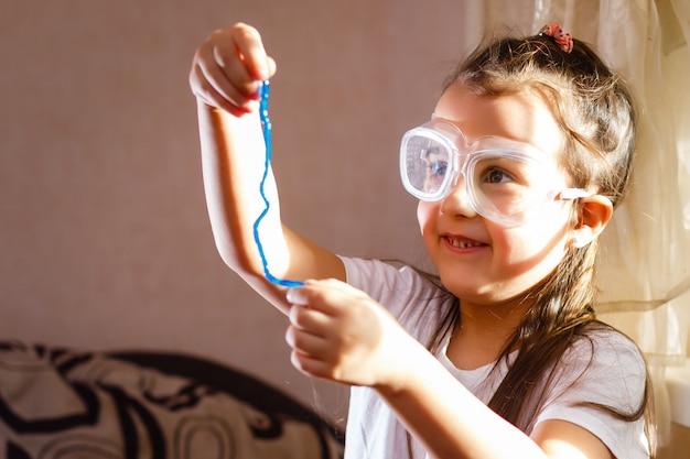 Kleines mädchen, das in der grundlegenden wissenschaftsklasse mit schutzhandschuhen und brille experimentiert