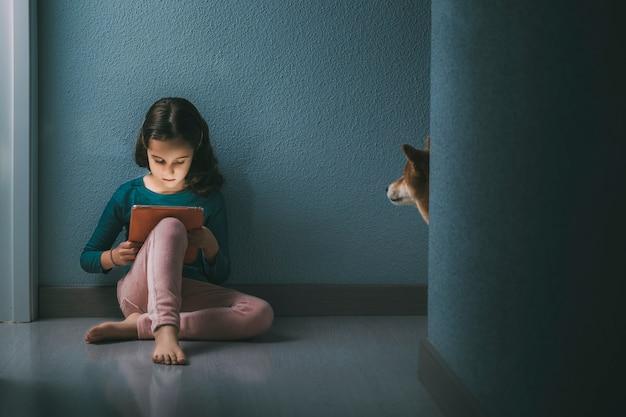 Kleines mädchen, das in der halle mit der tablette sitzt