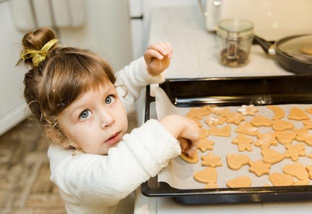 Kleines mädchen, das in der küche kocht