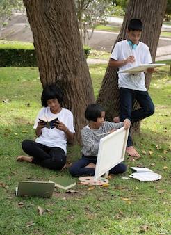 Kleines mädchen, das in der mitte der jüngeren schwester und ihres bruders sitzt. farbe auf leinwand malt. aktivität zusammen tun, hobby, in einem park