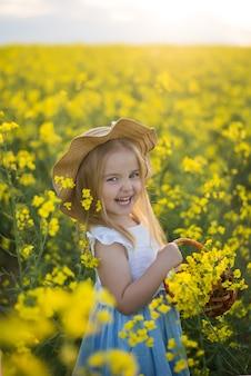 Kleines mädchen, das in einem feld, blumenkorb, lachendes rapsblumenfeld steht