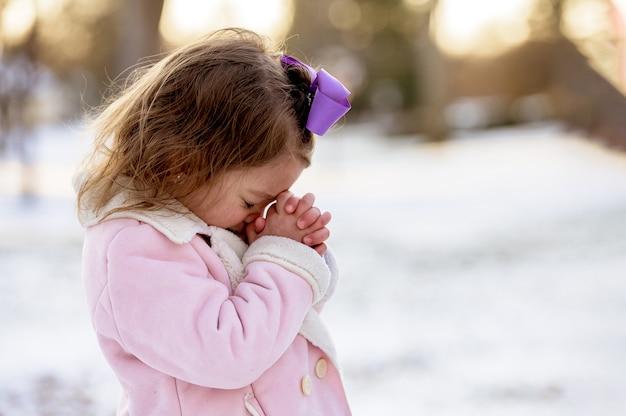 Kleines mädchen, das in einem garten betet, der mit dem schnee unter sonnenlicht mit einer verschwommenen entfernung bedeckt ist