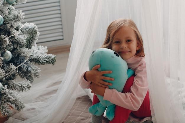 Kleines mädchen, das in einem kinderzimmer mit einem spielzeug sitzt