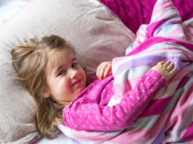 Kleines mädchen, das in einem rosa bett schläft
