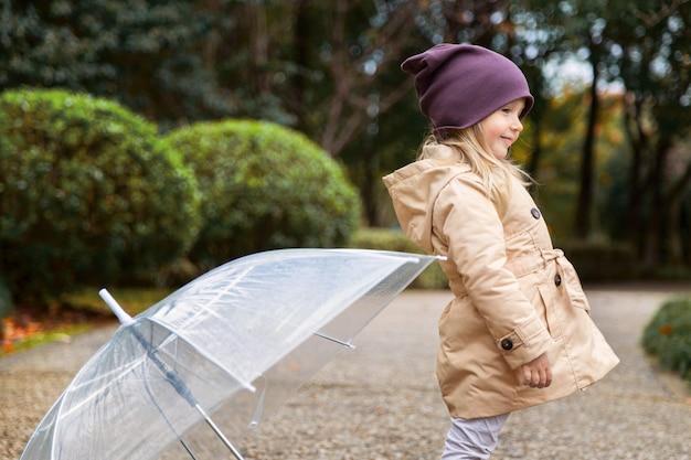 Kleines mädchen, das in einen park unter einen regenschirm während eines regens geht