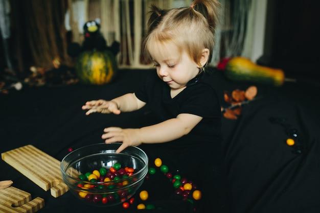 Kleines mädchen, das in einer hexe an halloween spielt