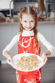 Kleines mädchen, das in einer küche mit plätzchen steht