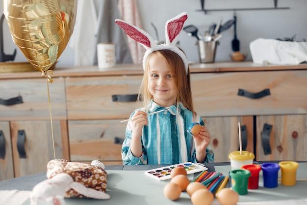 Kleines mädchen, das in einer küche sitzt