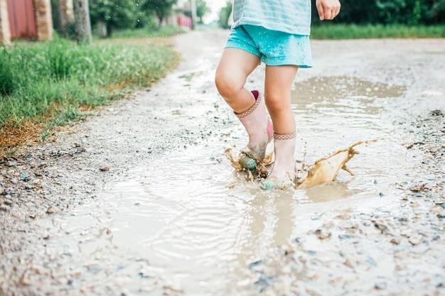 Kleines mädchen, das in einer pfütze an landstraße in gummistiefeln springt. sommerzeit, kindheit